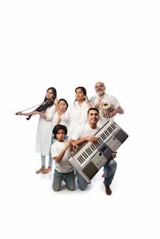 Concert van een indiase familie van zes die muziekinstrumenten bespeelt in een groep en een oudere dame die zingt, staande tegen een witte achtergrond