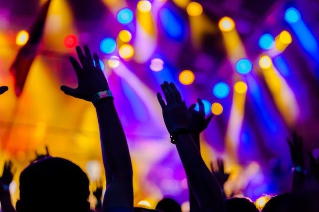 Concertmenigte met podiumverlichting op de achtergrond
