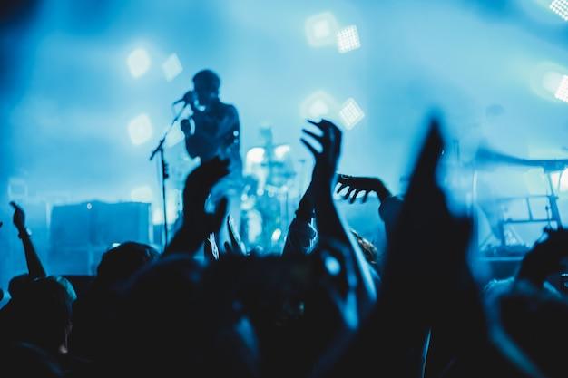 Concertpubliek dat een concert bijwoont, silhouetten van mensen zijn zichtbaar, verlicht door podiumlichten, opgeheven handen.