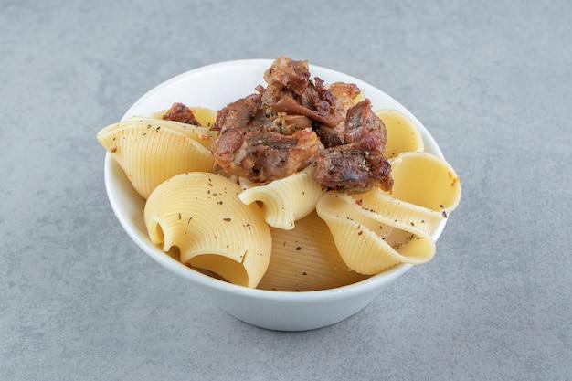 Conchiglie pasta met gegrilde kip in witte kom.