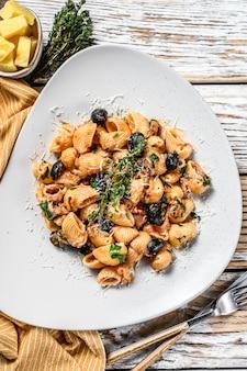 Conchiglie rigate italiaanse pasta met tomaat, olijven, kappertjes, ansjovis