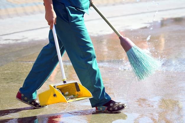 Conciërge reinigt de stoep van de stad. stad straatberoepen