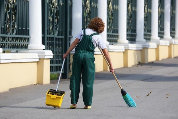 Conciërge reinigt de stoep van de stad van gevallen bladeren