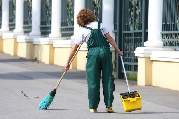 Conciërge reinigt het trottoir van de stad van gevallen bladeren. werk op het gebied van straatreiniging