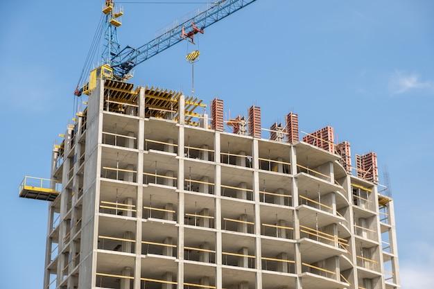Concreet kader van lang flatgebouw in aanbouw en torenkraan in een stad.