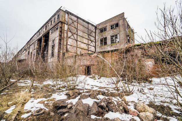 Concrete ruïnes in industrieel district. ruïnes van verlaten oude gebroken industriële fabriek of pakhuisgebouwen na ramp