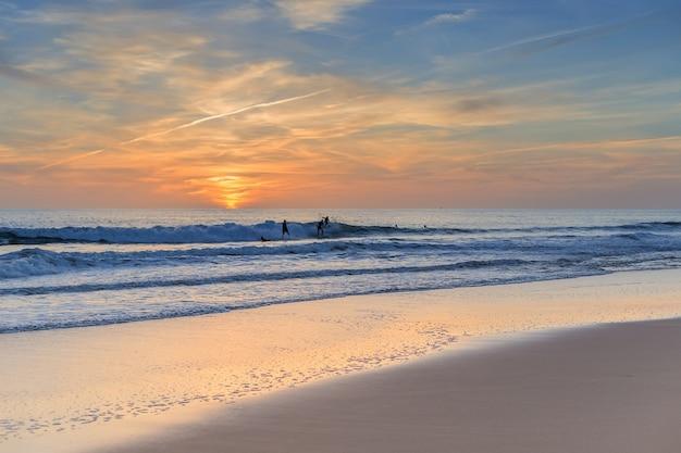 Concurrenten oefenden surfers bij zonsondergang.