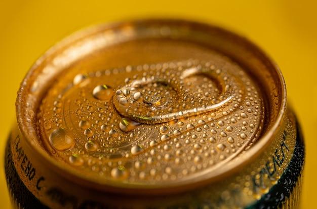 Condensaat op een koud metalen bierblikje op geel