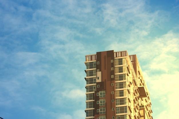 Condo met zonstijging licht aan zijaspect op blauwe hemel in ochtendglorie in bezit