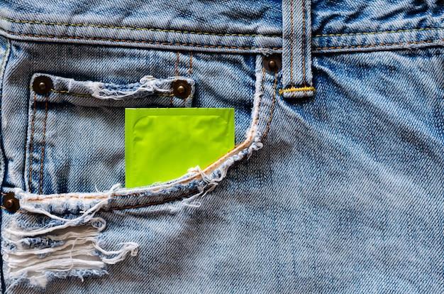 Condoom in jeanszak voor veilige seks, wereld seksuele gezondheid en aids-dagconcept.