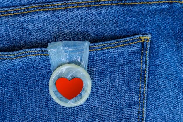 Condoom met een rood hart dat uit een jeanszak hangt. liefde en romantiek. veilige seks. valentijnsdag kaart.