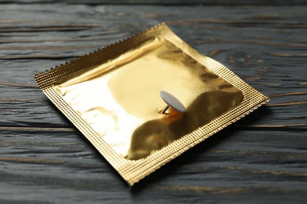 Condoom met pin op houten achtergrond, close-up