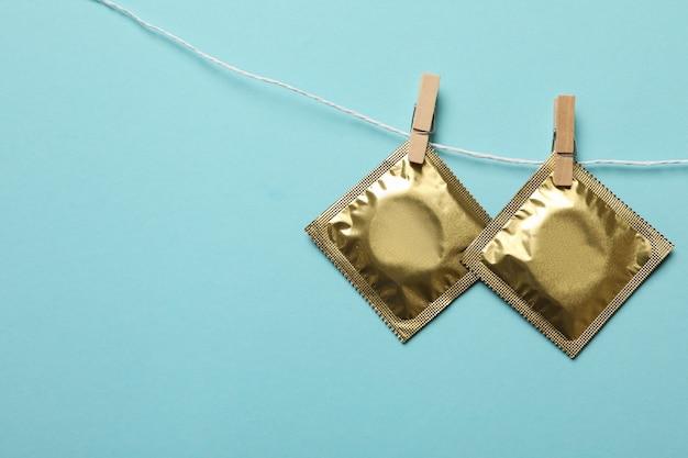 Condooms die aan het touw op blauwe ondergrond hangen