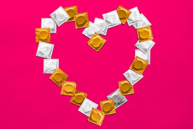 Condooms in hartvorm, bovenaanzicht. grote hoeveelheid condooms, schot van bovenaf - concept voor veilig vrijen en anticonceptie