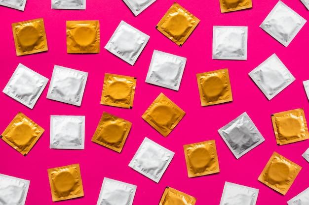Condooms in roze oppervlak, bovenaanzicht. grote hoeveelheid condooms, schot van bovenaf - concept voor veilig vrijen en anticonceptie