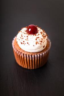 Confectiedessert eigengemaakte zwarte bos cupcake op een zwarte plaat van de leisteen