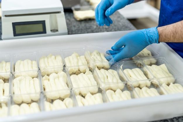 Confectors handen met desserts in plastic verpakking om het in te vriezen. industriële productie van voedsel