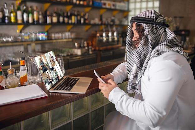 Conferentie. arabische zakenman die op kantoor werkt, zakencentrum met apparaat, gadget. moderne saoedische levensstijl. man in traditionele kleding en sjaal ziet er zelfverzekerd, druk, knap uit. etniciteit, financiën.