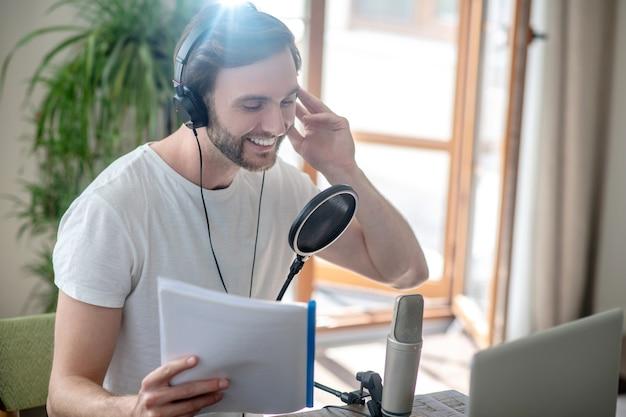 Conferentie. jonge, bebaarde man zit in een koptelefoon en spreekt in de microfoon