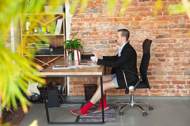 Conferentie. jonge man zonder broek maar in jas aan het werk op een computer, laptop. extern kantoor tijdens coronavirus, leuk en comfortabel in onderbroek. isolatie, quarantaine, humor, bedrijfsconcept.