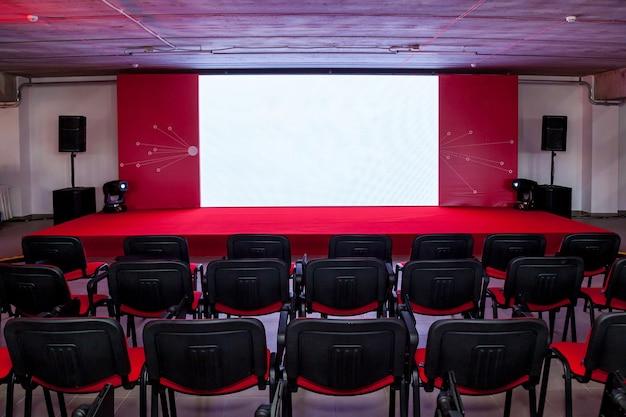 Conferentieruimte met een rood podium en rode stoelen voor evenementen, conferenties en seminars