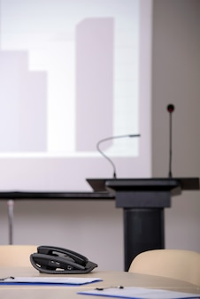 Conferentiezaal met tribune- en presentatieschermen.