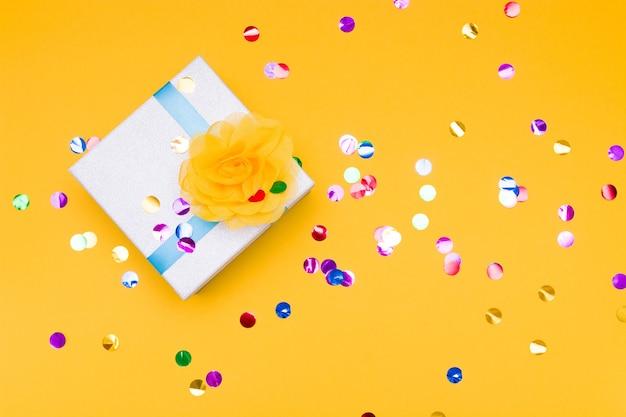 Confetti en geschenkdoos op gele achtergrond, kopie ruimte, bovenaanzicht