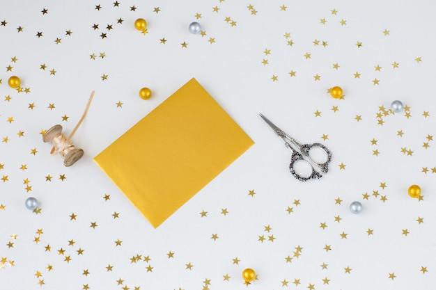 Confetti gouden sterren, gouden envelop, lint, schaar