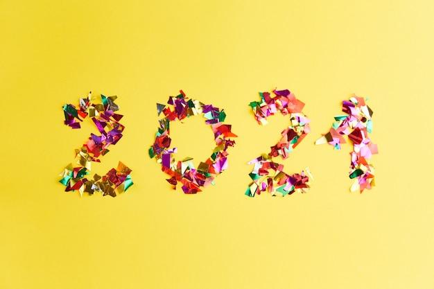Confetti in 2021-vorm op geel oppervlak