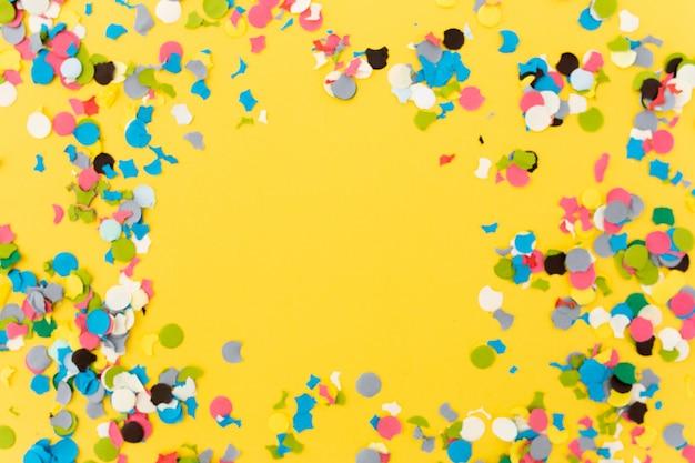 Confetti op gele achtergrond na het beëindigen van het feest