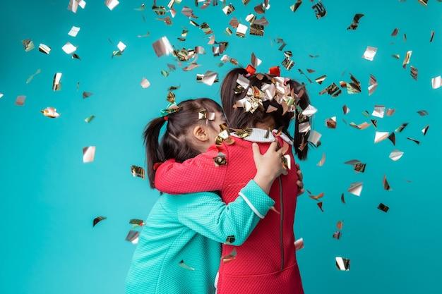 Confetti over hen heen. twee schattige meisjes met een psychische stoornis die samen gelukkig zijn tijdens het vieren van vakantie