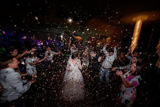 Confetti valt over bruidspaar dansen in donkere restaurantzaal
