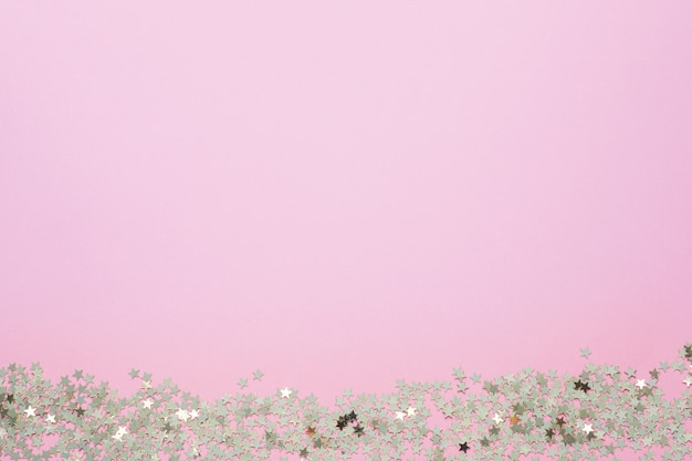 Confetti van gouden sterren glinsteren op een roze achtergrond. feestelijke vakantie