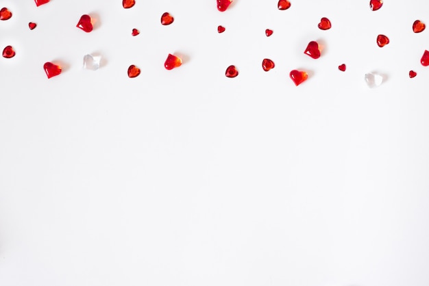 Confetti van rode harten. verspreiding van een in het nauw gedreven rand op een witte valentine-achtergrond