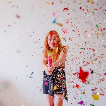 Confetti vliegen in lucht en meisje achter