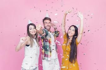 Confettien die over vrienden vallen die tegen roze achtergrond genieten van