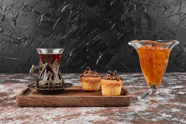 Confituur, muffins en een glas thee op een houten bord.
