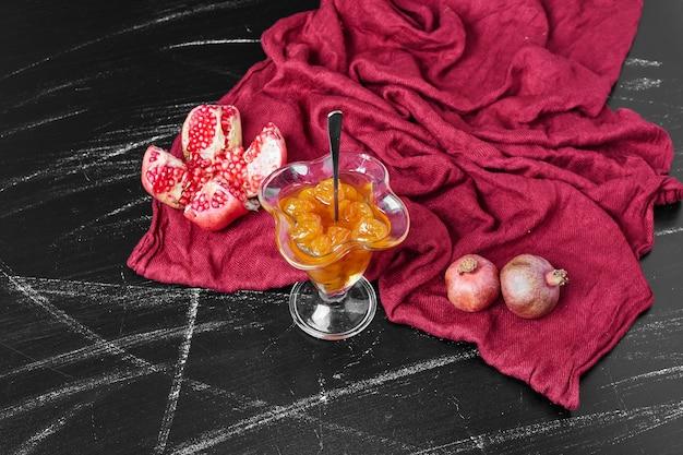 Confituur op rode handdoek met granaatappel.