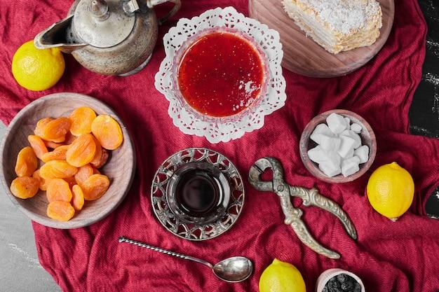 Confituur op rode handdoek met thee.