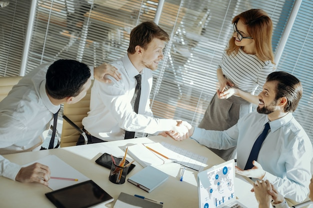 Conflict opgelost. aangename mannelijke kantoormedewerkers die elkaar de hand schudden, zich met elkaar verzoend met de hulp van hun collega's en een teamleider