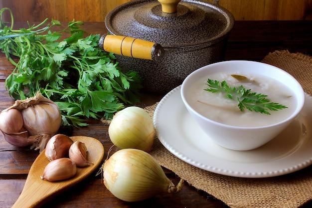 Congee in ceramische kom op rustieke houten lijst, traditionele rijsthavermoutpap typisch van aziatische keuken