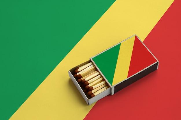 Congo vlag wordt getoond in een open luciferdoosje, dat gevuld is met lucifers en op een grote vlag ligt