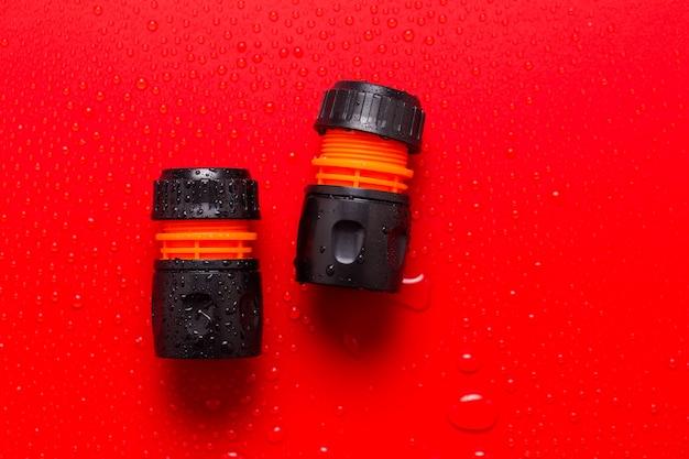 Connector voor het besproeien van de tuin op rood met waterdruppels.