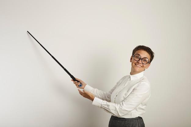 Conservatief geklede blanke vrouwelijke leraar in lelijke ronde glazen met een wijzer naar een leeg whiteboard en onaangenaam lachend