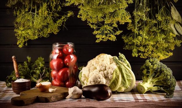 Conservering van groenten. op de tafel staat een pot tomaten, een zoutvaatje, knoflook, uien, bloemkool, broccoli. er hangen trossen dille overheen.