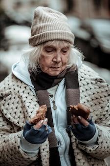 Constante honger. depressieve, trieste dakloze vrouw die naar de stukjes brood kijkt terwijl ze aan ondervoeding lijdt