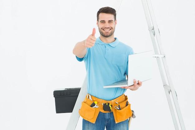 Construciton werknemer met laptop gesturing duimen omhoog
