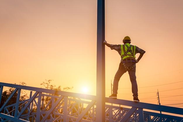 [constructie van veiligheidslichaam] ingenieur die in een metalen dakconstructie werkt, bouwingenieur draagt veiligheidsuniform op hoogte inspectie van metalen uitrusting voor industriële dakbedekking.