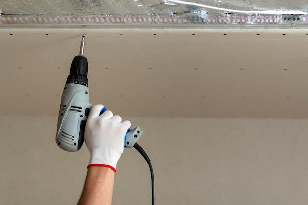 Constructor werknemer hand in beschermende handschoen met elektrische draadloze schroevendraaier