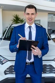 Consultant bewaart documenten op de achtergrond van auto's